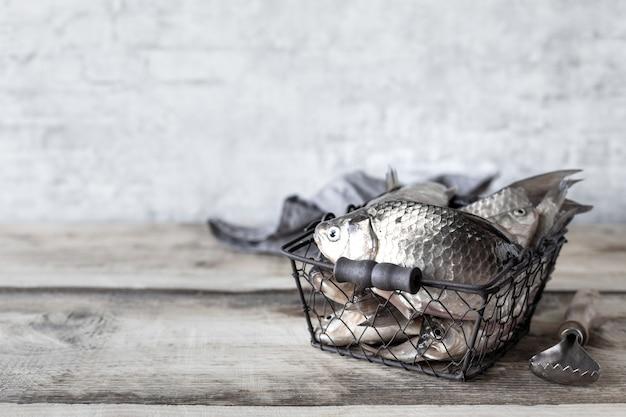 Roher frischer flussfisch in einer schüssel auf einem holztisch