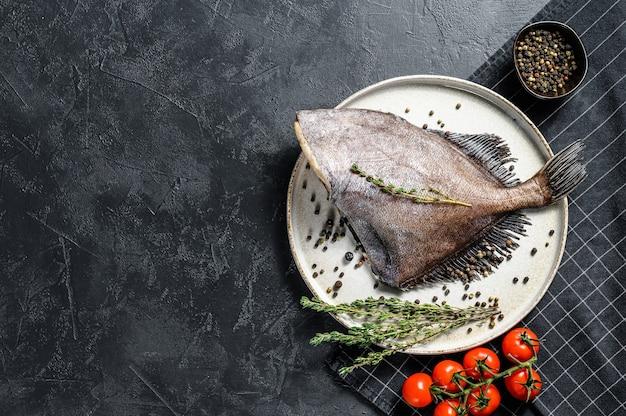 Roher frischer john dory fisch mit gewürzen und kräutern zum kochen. schwarzer hintergrund