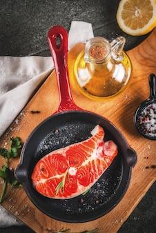 Roher frischer lachsfisch mit bestandteilen für das kochen des olivenöls, der zitrone, der zwiebel, der petersilie, des rosmarins, auf bratpfanne, schwarze steintabelle, draufsicht copyspace
