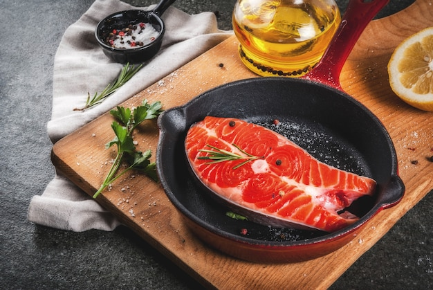 Roher frischer lachsfisch mit bestandteilen für das kochen des olivenöls, der zitrone, der zwiebel, der petersilie, des rosmarins, auf bratpfanne, schwarzer steintabelle, copyspace