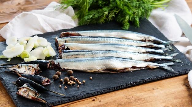 Roher frischer nadelfisch (belonidaefamilie) auf der platte kochfertig