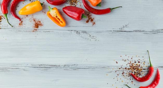 Roher frischer organischer roter chilipfeffer und verschiedene gewürze auf weißem hölzernem hintergrund