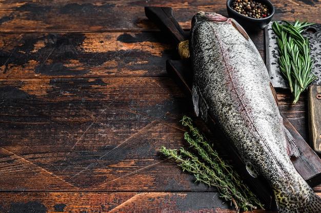 Roher frischer regenbogenforellenfisch mit kräutern. dunkler hölzerner hintergrund. draufsicht. speicherplatz kopieren.