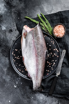 Roher ganzer forellenfisch ohne kopf, mit salz und rosmarin