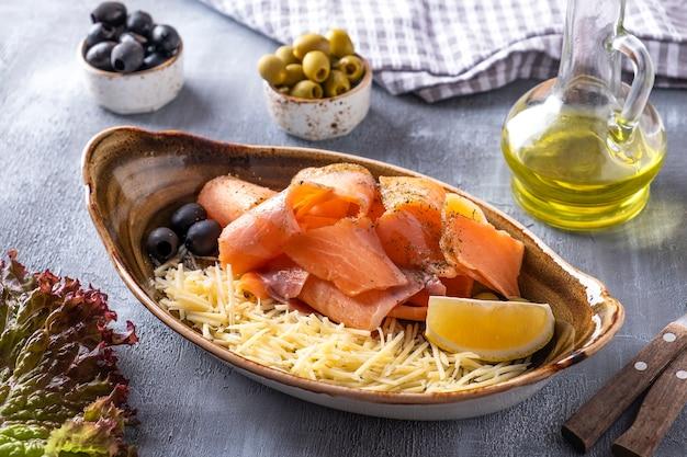 Roher gefrorener lachs - stroganina. roher gefrorener fisch mit käse, zitrone und oliven auf einem teller.