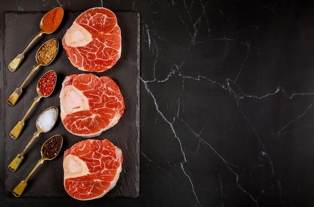 Roher gekreuzter rindfleischschenkel und gewürze auf tafel.