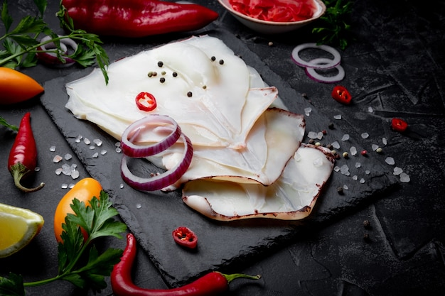 Roher geschälter tintenfisch und gewürze zum kochen auf einem schieferbrett und einer schwarzen oberfläche. nahansicht.
