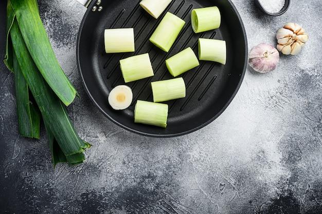 Roher geschmorter lauch auf grillpfanne ungekocht mit kräuterbestandteilen, auf strukturiertem grauem hintergrund draufsicht mit raum für text.