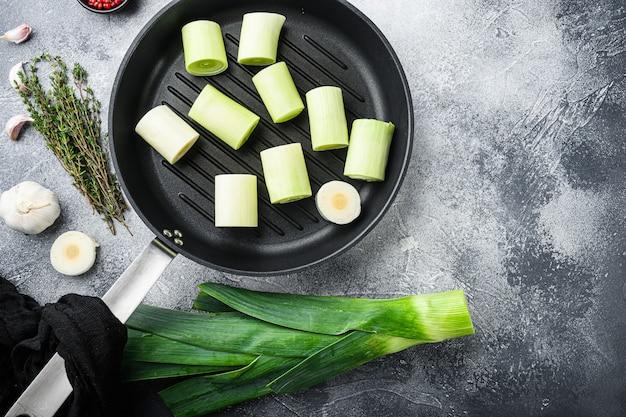 Roher geschmorter lauch auf grillpfanne ungekocht mit kräuterzutaten, auf strukturierter grauer tischoberansicht.