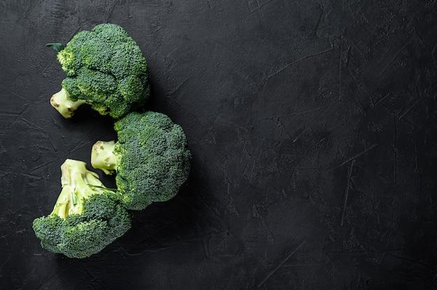 Roher grüner brokkoli auf einem schwarzen hintergrund. ansicht von oben. platz für text