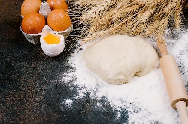 Roher hefeteig in schüssel und zutaten, eier, mehl, weizenähren auf dunklem tisch, backkonzept