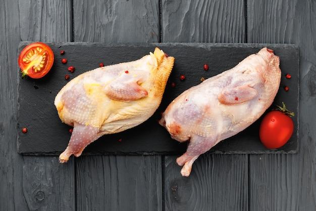 Roher hühnerkadaver auf hölzernem teller nah oben