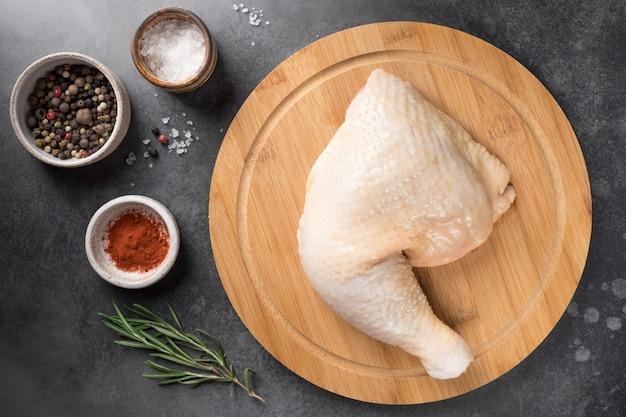 Roher hühnerschenkel auf holzbrett und gewürzen auf dunklem hintergrund frisches fleisch
