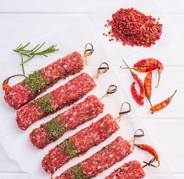 Roher kebab mit gewürzen auf einem schwarzen tisch