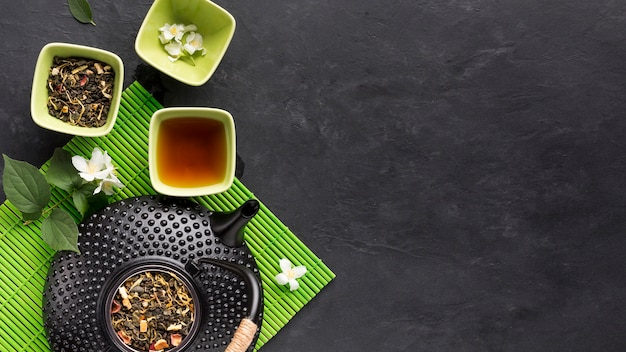 Roher kräuterteebestandteil mit teekanne auf grünem tischset über schwarzer oberfläche