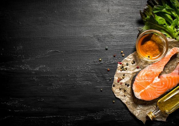 Roher lachs mit olivenöl, gewürzen und kräutern an schwarzer tafel.