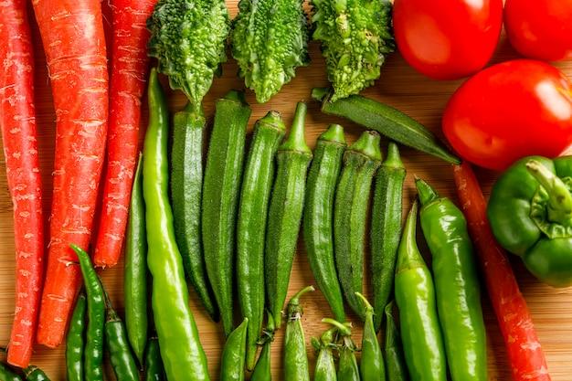 Roher ladyfinger und anderes gemüse auf holzbrett