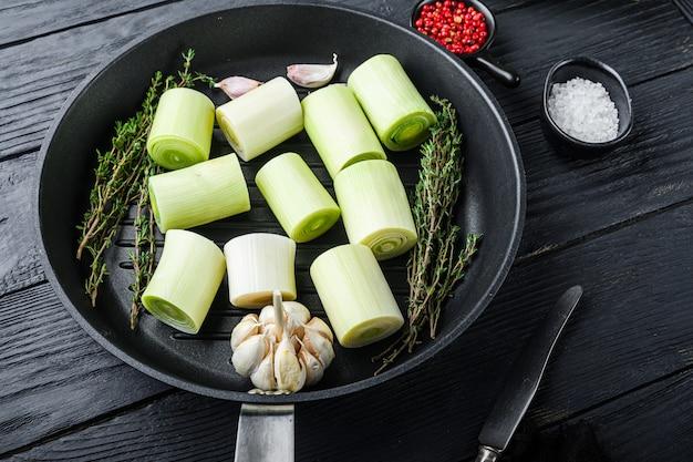 Roher lauch sultan gehackt oninon auf grillpfanne ungekocht mit kräuterzutaten, auf schwarzem holztisch seitenansicht.