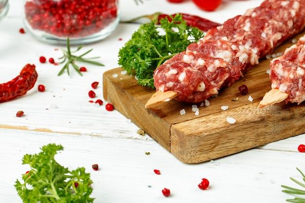 Roher lula-kebab am spieß mit gewürzen auf holzbrett