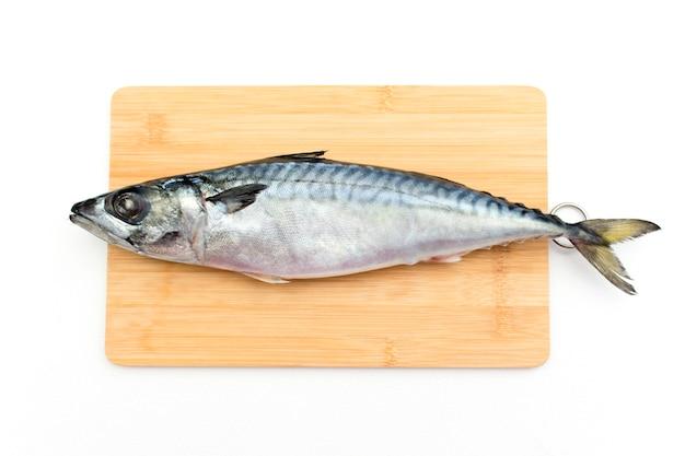 Roher makrelenfisch liegt auf einem holzbrett.