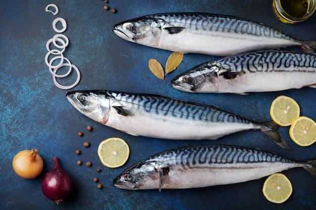 Roher makrelenfisch mit zutaten zum kochen auf einer blauen betonoberfläche