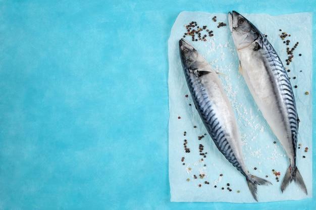 Roher makrellefisch mit bestandteilen für das kochen auf blau.