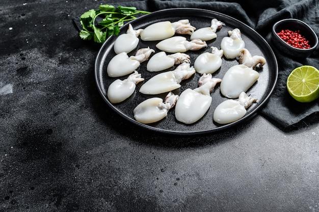Roher mini-tintenfisch mit rosmarin und petersilie auf einem teller