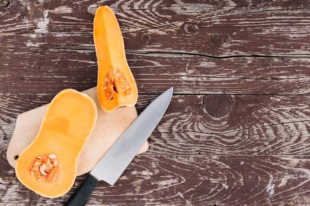 Roher orange organischer moschuskürbis auf hackendem brett mit messer über dem hölzernen schreibtisch