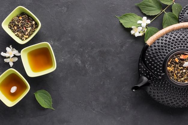 Roher organischer gesunder tee und es sind bestandteil auf schwarzer oberfläche