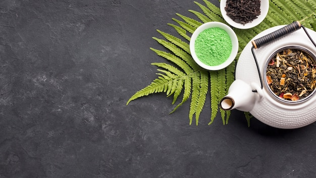 Roher organischer grüner matchatee in der schüssel mit trockenem teebestandteil