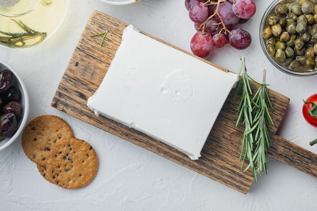 Roher organischer weißer feta-käse-satz, auf weißem tisch, draufsicht