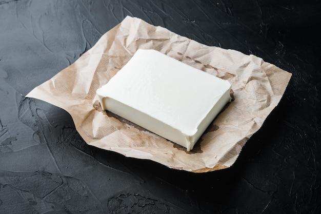 Roher organischer weißer feta-käsesatz, auf schwarzem hintergrund
