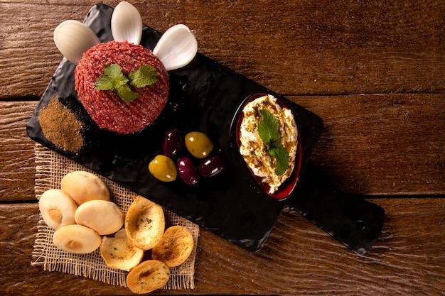 Roher quibe, garniert mit minze, hummus, baba ganoush, zwiebel und brot.