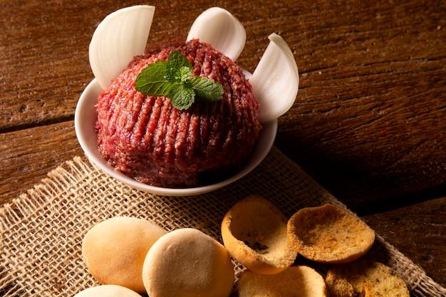 Roher quibe, garniert mit minze, tomate, zwiebel und salat.