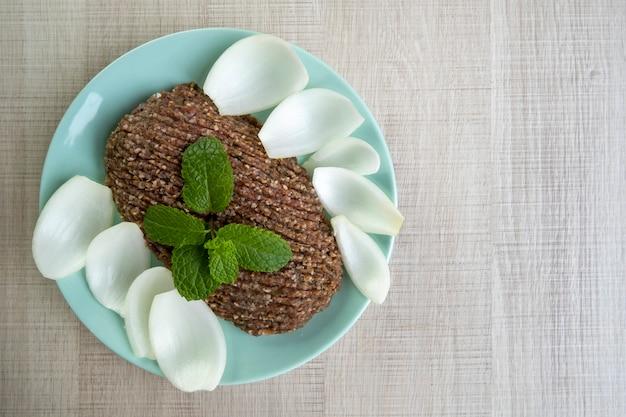 Roher quibe mit geschnittenen zwiebeln und einem zweig minze.