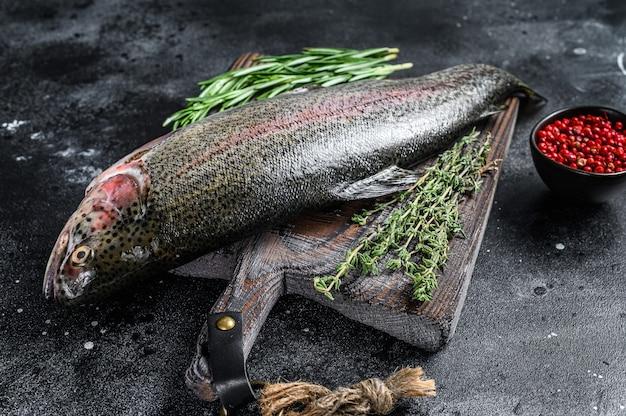 Roher regenbogenforellenfisch auf einem schneidebrett mit kräutern. schwarzer hintergrund. draufsicht.