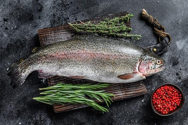 Roher regenbogenforellenfisch auf einem schneidebrett mit kräutern
