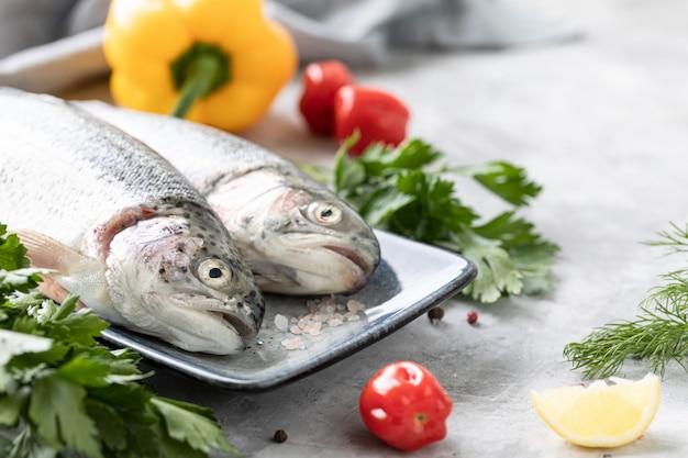 Roher regenbogenforellenfisch auf einem teller, gemüse und frisches gemüse für die zubereitung gesunder und schmackhafter speisen. gesunde ernährung und leckeres kulinarisches konzept.