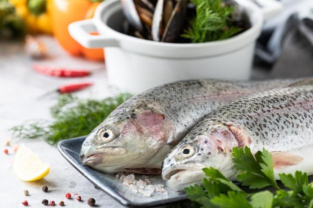 Roher regenbogenforellenfisch auf einem teller, gemüse und frisches gemüse für die zubereitung gesunder und schmackhafter speisen.
