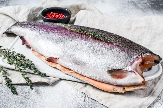 Roher regenbogenforellenfisch mit salz und thymian.