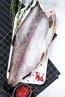 Roher regenbogenforellenfisch mit salz und thymian