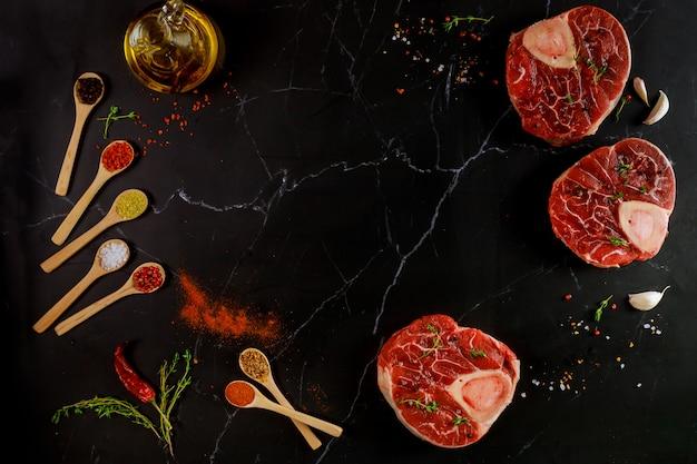 Roher rindfleischschenkel und gewürze für die zubereitung des ossobuco-gerichts auf schwarzem hintergrund. draufsicht.