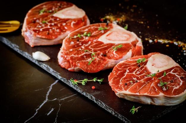 Roher rindfleischschenkel und gewürze für die zubereitung von ossobuco-schalen auf schwarzer oberfläche