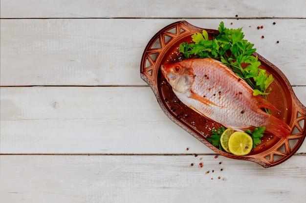 Roher roter tilapia-fisch mit kräutern und zitrone und limette auf weißem hölzernem hintergrund. draufsicht, kopierraum.