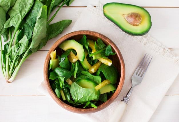 Roher salat des spinats, der avocado und der orange in der hölzernen platte auf weißem hintergrund