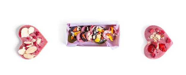 Roher schokoriegel mit getrockneten früchten und nüssen auf weißem hintergrund. hochwertiges foto