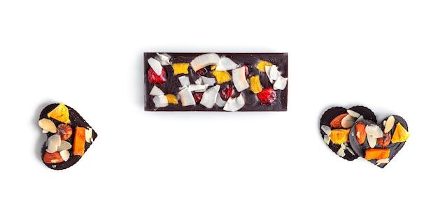 Roher schokoriegel mit getrockneten früchten und nüssen auf weißem hintergrund
