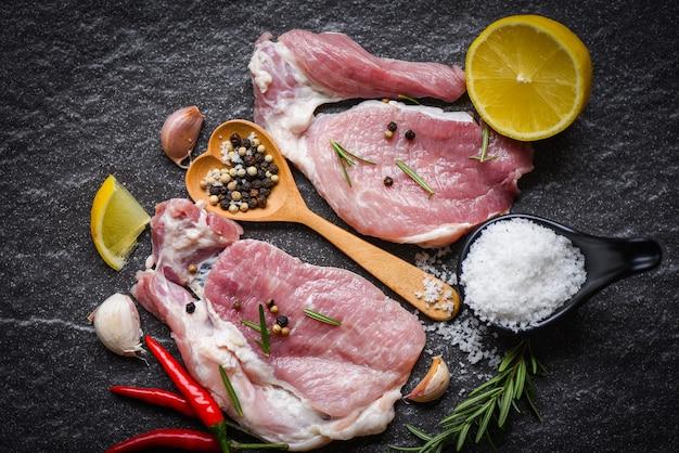Roher schweinefleisch rosmarin auf schwarzem teller mit kräutern und gewürzen zitronenpfeffer knoblauchsalz