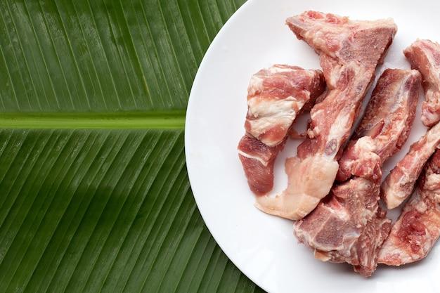 Roher schweineknochen in weißer platte auf bananenblatt