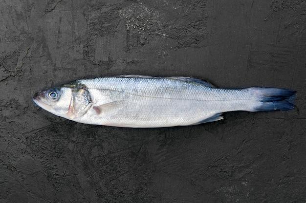 Roher seebarschfisch auf schwarzem steintisch